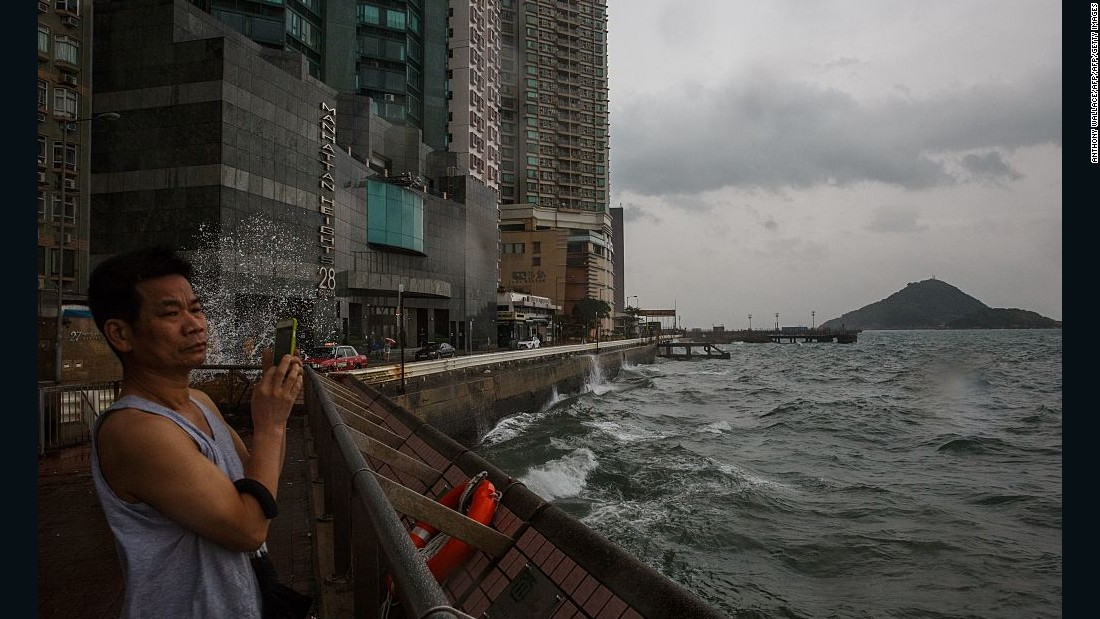 A man takes photos while looking out on the rough waters of Victoria Harbor as Typhoon Haima approaches Hong Kong on October 21, 2016