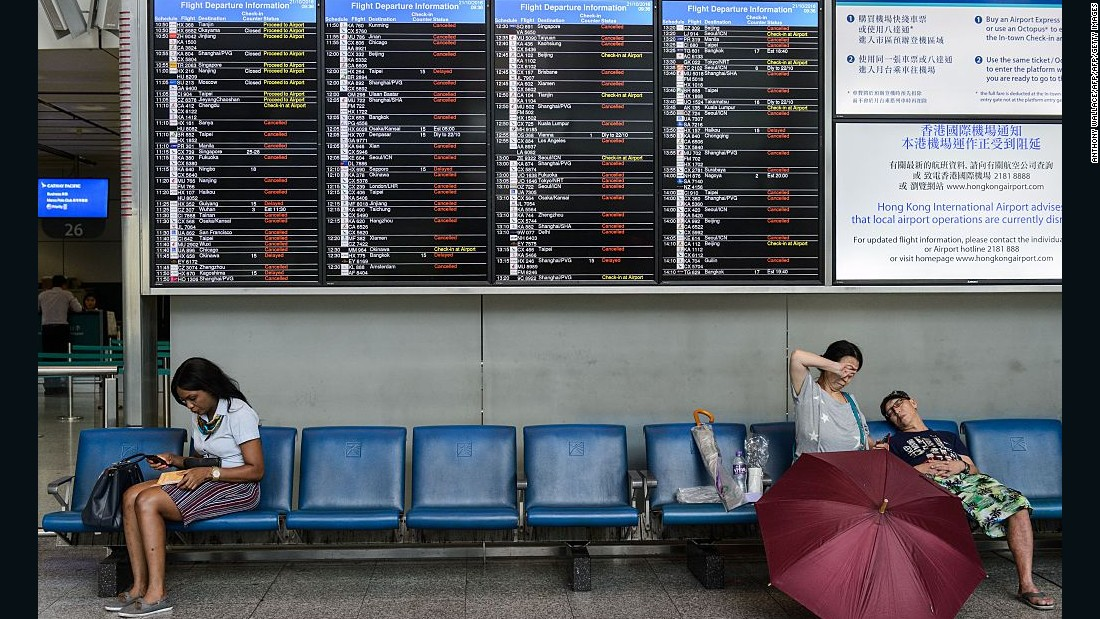 People wait under displays showing lists of canceled and delayed flights at the Airport Express station as Typhoon Haima approaches Hong Kong.