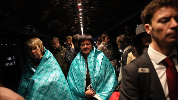 Passengers wear emergency blankets to keep warm outside the terminal.