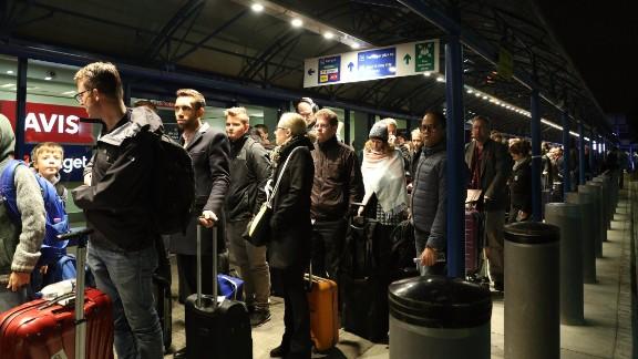 Passengers queue outside terminal.