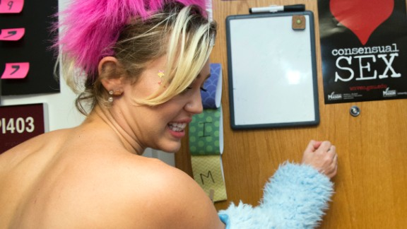 Miley Cyrus knocks on the door of a dorm room while campaigning for Democratic presidential nominee Hillary Clinton at George Mason University in Fairfax, Virginia, on Saturday, October 22,