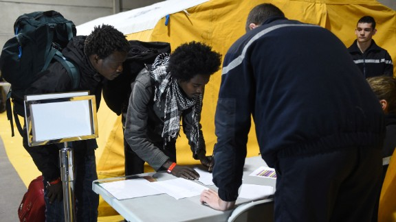 Migrants register with French authorities on October 24 before boarding buses that will transport them to shelters across France.