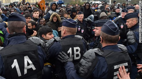 French riot police officers hold back migrants Monday as an operation began to clear the camp.