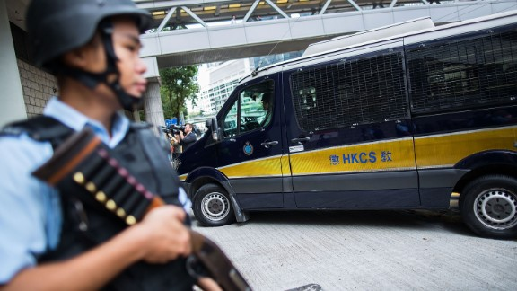 Police officers stand guard as British banker Rurik Jutting arrives at court on October 24.