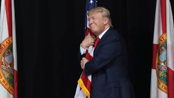Donald Trump hugs the American flag as he arrives for a campaign rally at the MidFlorida Credit Union Amphitheatre on October 24, 2016 in Tampa, Florida.