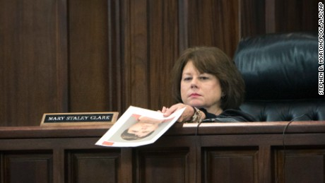Cobb County Superior Court Judge Mary Staley Clark holds a booking mug shot of Justin Ross Harris.