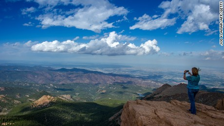 A woman takes a picture at the top of Pikes Peak mountain in the Rocky Mountains.