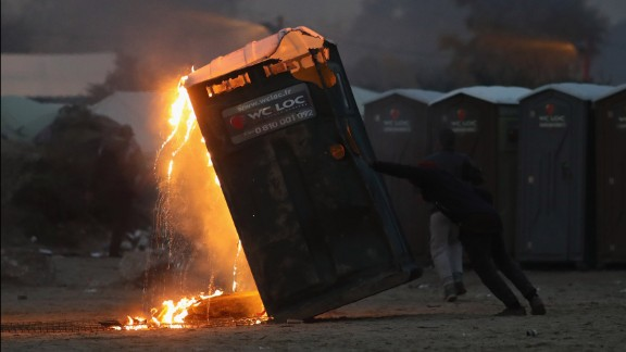 A migrant sets fire to a portable toilet inside the camp on Monday, October 24.