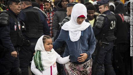 Refugees get ready to leave Calais as demolition begins at the Jungle migrant camp Tuesday.