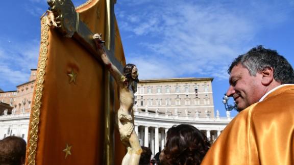 A pilgrim holding a crucifix attends the Pope