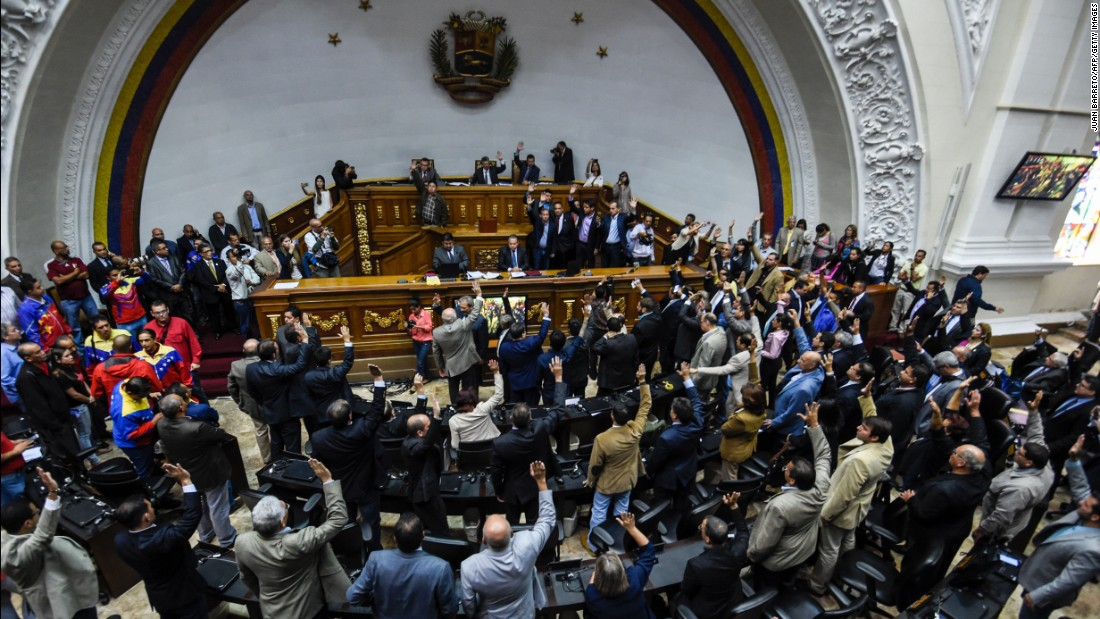 "Opposition deputies raise their hands while voting to open a political trial against President Nicolas Maduro. A majority of lawmakers voted in favor of a motion to launch a ""political and criminal trial"" after his government blocked their drive for a referendum on removing him."