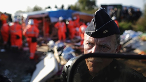 A police officer guards demolition crews as they work to dismantle the site on October 25.