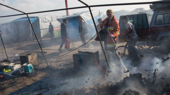 A firefighter extinguishes a fire set to migrants