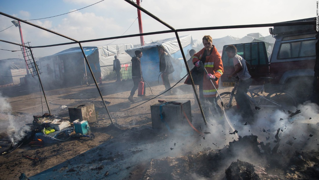 A firefighter extinguishes a fire set to migrants' tents during the mass evacuation.