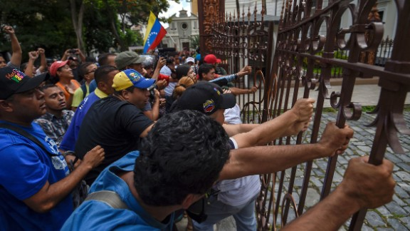 Supporters of Maduro break the gate and force their way to the National Assembly during an extraordinary session called by opposition leaders. Each side accuses the other of staging a coup in the country, which is in the midst of economic and political strife.