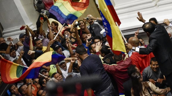 Supporters of President Nicolas Maduro wave flags and shout as they force their way into the National Assembly floor during a meeting of the opposition-led congress in Caracas on Sunday, Oct. 23, 2016. The four-hour extraordinary session was interrupted for about 30 minutes after government supporters breached security and threatened lawmakers on the National Assembly floor.