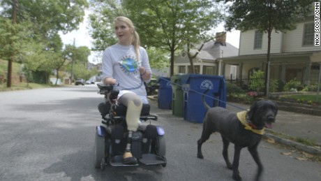 Flesh-eating bacteria survivor Aimee Copeland rides her wheelchair down an Atlanta street with her service dog, Belle, on April 11, 2016.