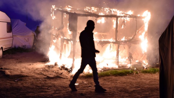A migrant walks past a burning shack that was set on fire, as a demolition crew began tearing structures down on Tuesday, October 25.