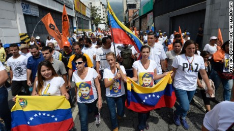 Lilian Tintori (2-L), wife of prominent jailed opposition leader Leopoldo Lopez, holds a Venezuelan national flags as she marches against the government of President Nicolas Maduro in the streets of Caracas on October 26, 2016.
