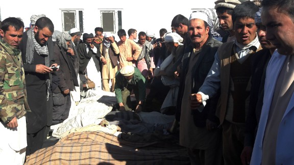 Afghan men gather around the bodies of civilians killed by ISIS militants on October 26.