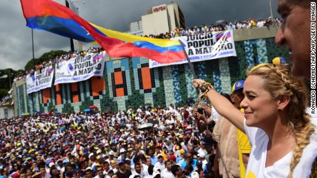 Lilian Tintori, wife of prominent jailed opposition leader Leopoldo Lopez, waves a Venezuelan national flag during a rally against the government of President Nicolas Maduro in Caracas on October 26, 2016.  Opponents of Maduro rallied in the streets as the leftist leader convened a crisis security meeting resisting their efforts to drive him from power. Thousands of opposition supporters began to gather at seven points around Caracas in the morning planning to march and join up in the east of the capital.  / AFP / Ronaldo SCHEMIDT        (Photo credit should read RONALDO SCHEMIDT/AFP/Getty Images)