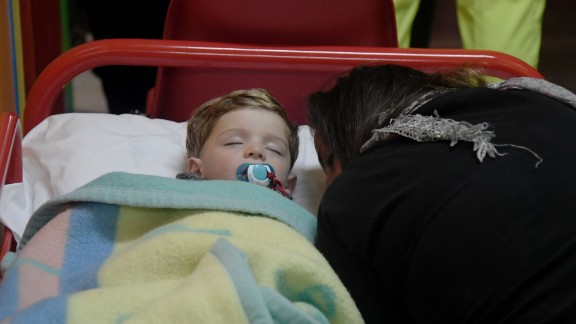 A child sleeps in a secured area of Visso after earthquakes rocked central Italy.