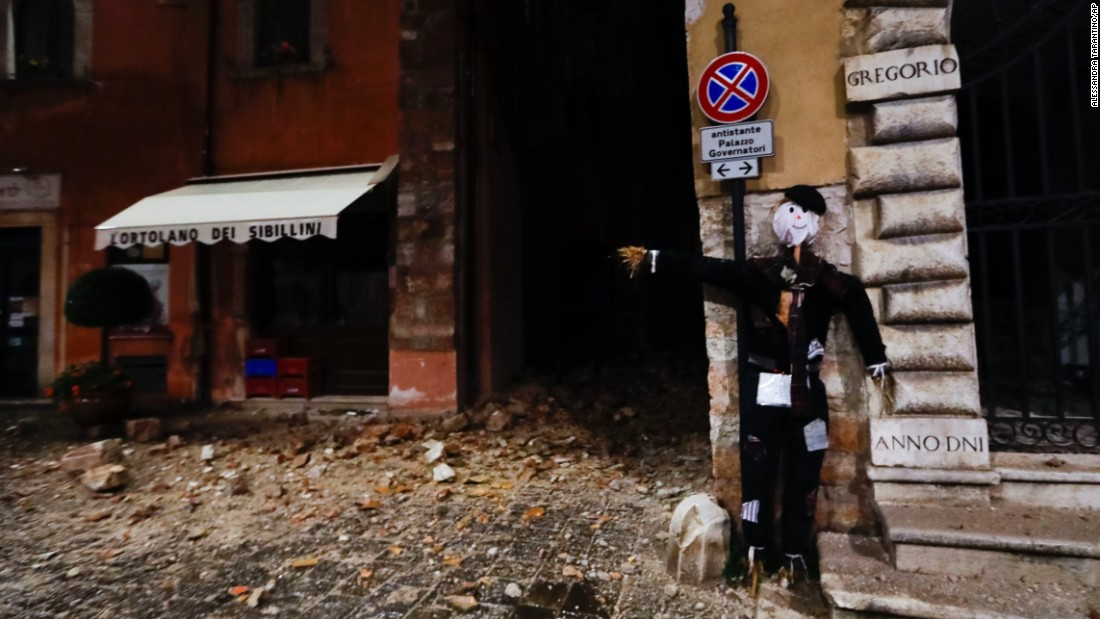 A Halloween dummy rests on a wall in front of earthquake damage in Visso.