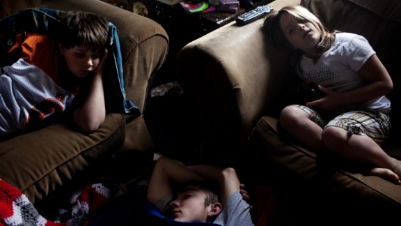 William Sellers, left, and one of his sisters lie on a sofa as their visiting cousin, Dominic, sleeps on their floor in Columbus, Ohio, in 2010. The family moved from Chauncey to Columbus so the twins could attend a school for deaf children.