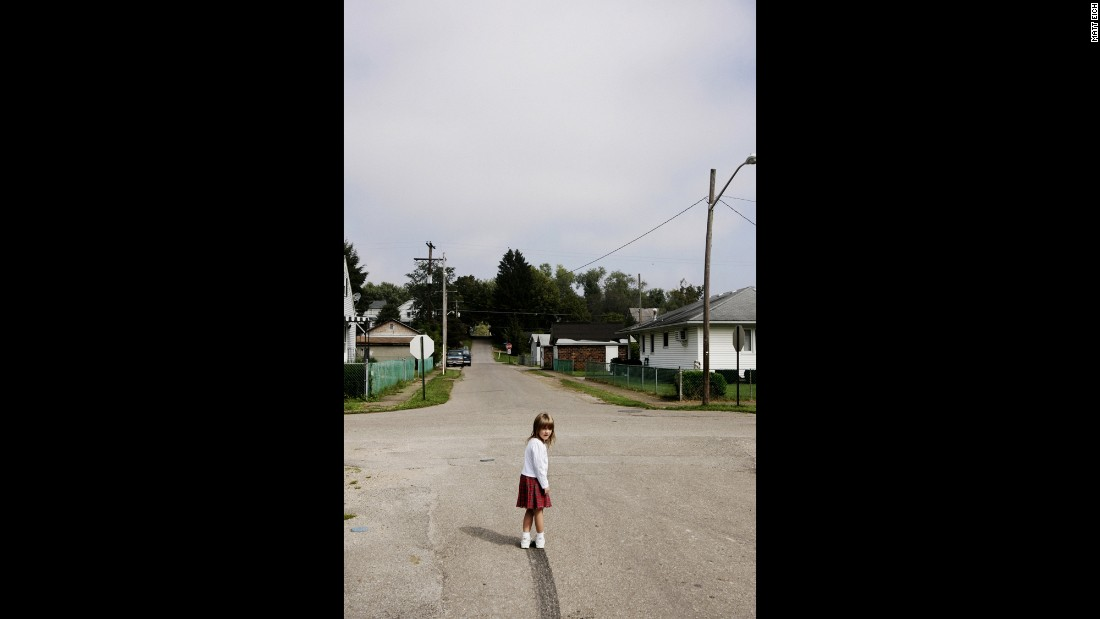 "Lacey wanders out in the middle of the street to examine the skidmark her dad left as he drove away one day. At the time, Eich said, he couldn't put his finger on what struck him about the photo. The realization came later, when the photographer had children of his own. ""In the photo, there's some uncertainty to the road; you can't really see where it leads. It makes me think of the opportunities my daughters have, compared to those that the twins have."""