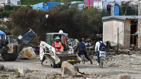 Two people cycle past a man driving a bulldozer in The Jungle camp in Calais, on October 27, 2016.