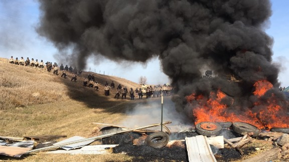 Tires burn as authorities try to force force Dakota Access Pipeline protesters off private land where they had camped to block construction.