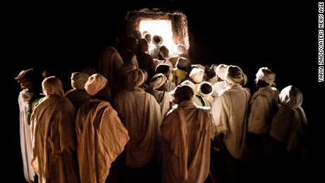 Pilgrims waiting to emerge from inside a tunnel at Bet Girogis or the House of St George, Lalibela, Ethiopia. This hand-carved, 12th century church is connected to 12 other churches by a series of tunnels, designed to protect medieval worshipers from attacks, but also to symbolize the movement of pilgrims from darkness to light.