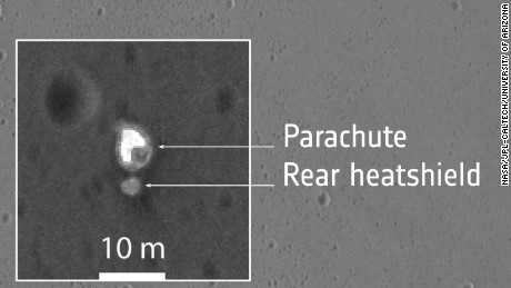 The zoomed insets provide close-up views of what are thought to be several different hardware components associated with the Schiaparelli module's descent to the martian surface.