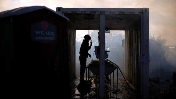 A migrant shaves while cleaning crews continue demolition of the Jungle on October 27