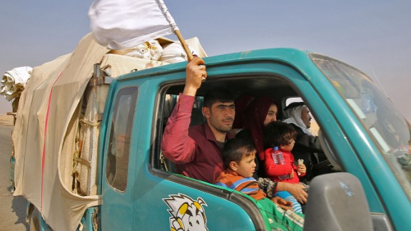 An Iraqi man waves a white flag as his family flees the fighting Thursday.