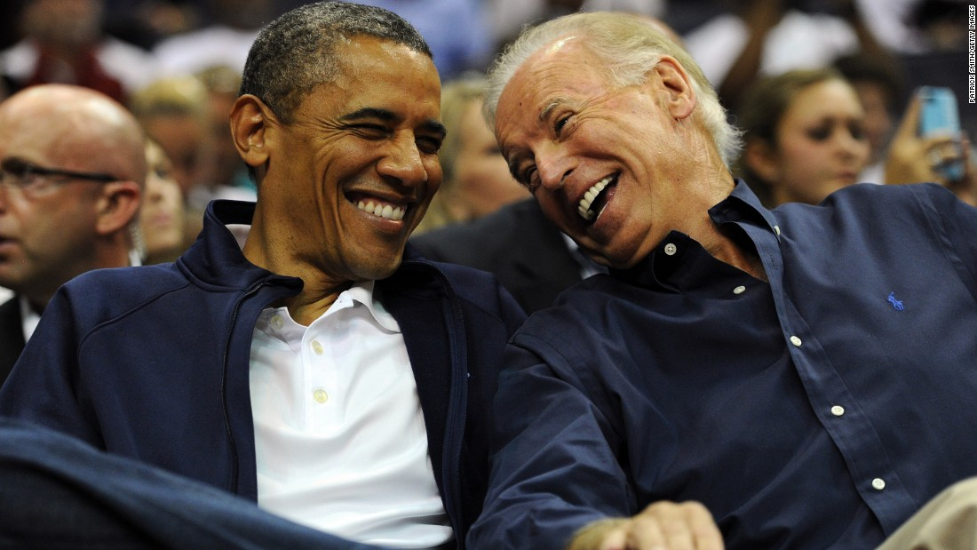 Obama and Biden laugh together as they attend a basketball game in July 2012.