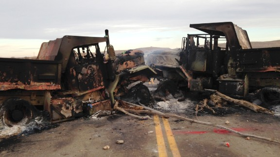 The burned hulks of heavy trucks sit on Highway 1806 near Cannon Ball, N.D., on Friday, Oct. 28, near the spot where protesters of the Dakota Access pipeline were evicted from private property a day earlier. Authorities say protesters burned several pieces of construction equipment Thursday during a chaotic confrontation with law enforcement.