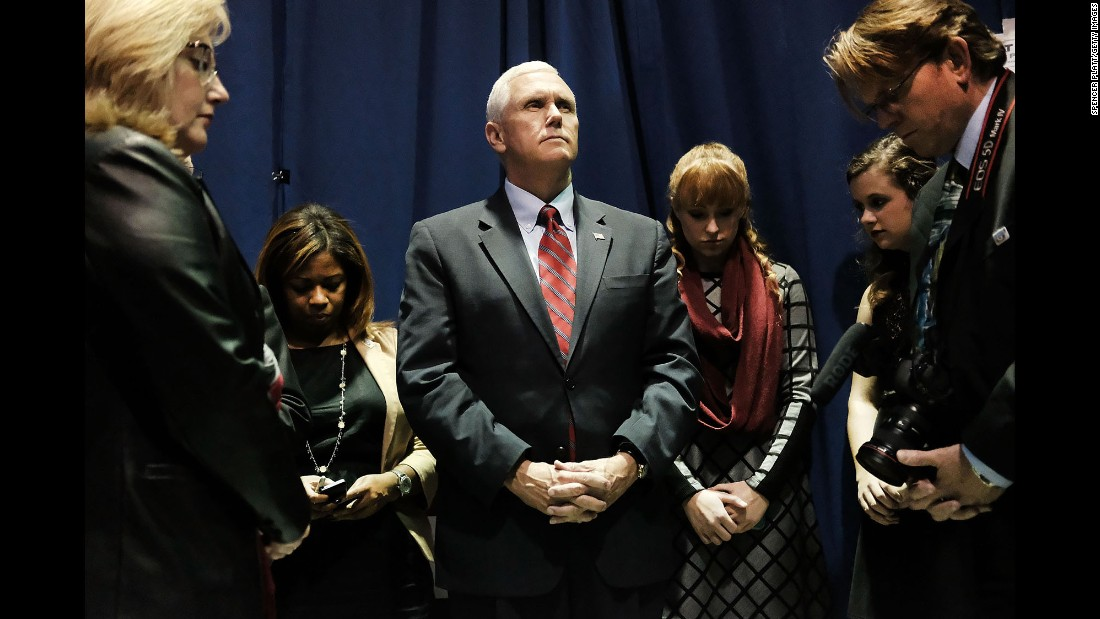 Indiana Gov. Mike Pence, Donald Trump's running mate, prays with his staff before taking the stage in Marietta, Ohio, on Tuesday, October 25.