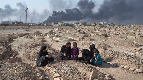 Women and children grieve over the grave of a family member at a Qayyara cemetery damaged by ISIS on October 27.