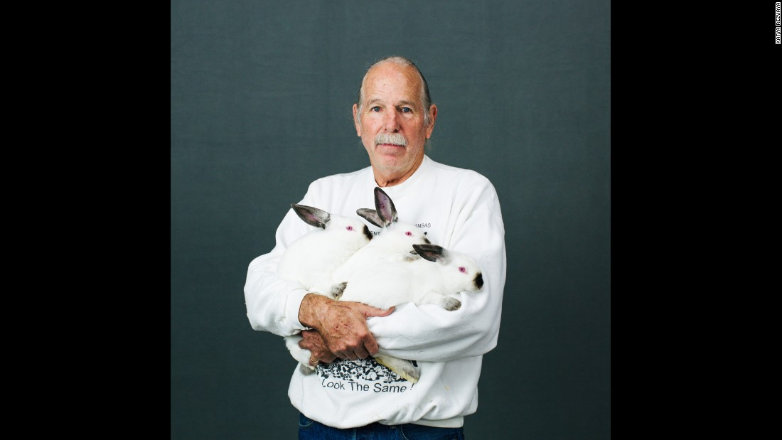Rob Fender, a breeder from Julian, California, holds three Californian rabbits. He names all of his rabbits with numbers.