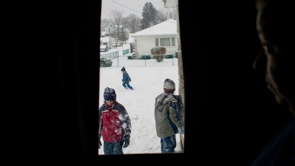 Tracy Sellers watches her kids play with neighbors in the front yard of their home in Chauncey, Ohio, in 2007. Chauncey