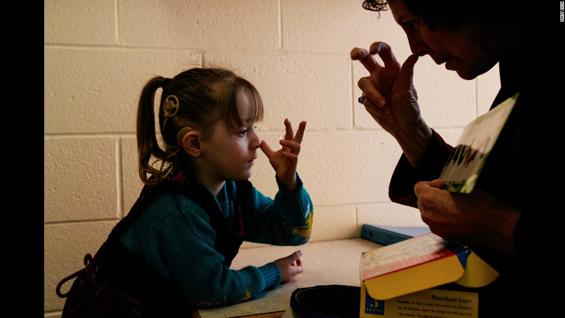 "School therapist Pattie O'Brien makes the sign for ""bug"" with Lacey during one-on-one-tutoring in 2006."