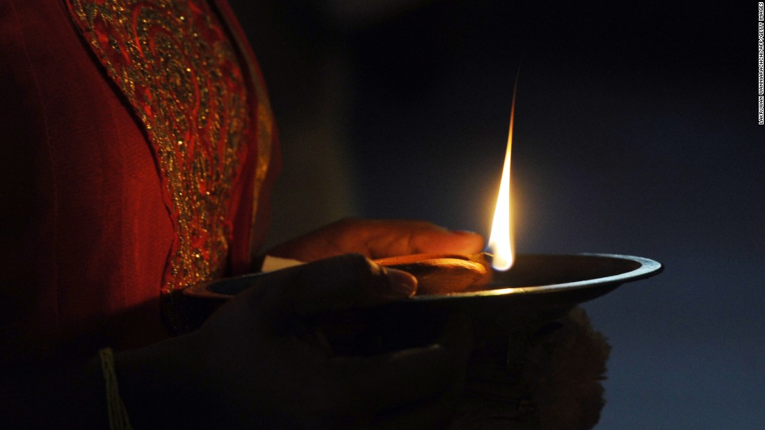 A woman holds an oil lamp while offering prayers in Colombo, Sri Lanka, on October 29.