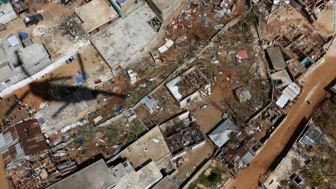 "A helicopter passes over damaged houses in southwestern Haiti as the U.S. military delivers rice for <a href=""http://www.cnn.com/2016/10/07/world/gallery/haiti-hurricane-matthew/index.html"" target=""_blank"">Hurricane Matthew</a> relief on Thursday, October 13."