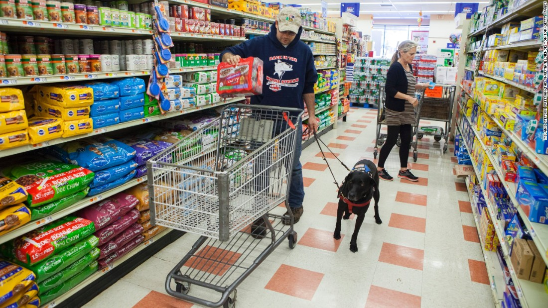 U.S. veteran Donnie Jarvis shops with his service dog, Mocha, in Newbury, Massachusetts, on Wednesday, October 12. Jarvis served in Iraq and Afghanistan and met Mocha through Operation Delta Dog, which teams rescued dogs with veterans who suffer from post-traumatic stress disorder or traumatic brain injuries.
