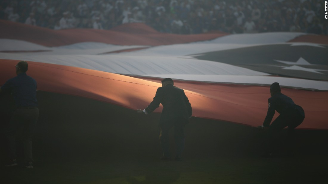Military personnel hold an American flag in Los Angeles before Game 3 of the National League Championship Series on Tuesday, October 18.
