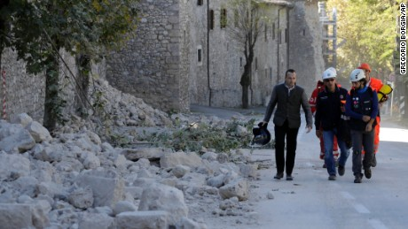 Italian civil protection staff pass a collapsed wall Sunday in Norcia after the quake jolted central Italy.