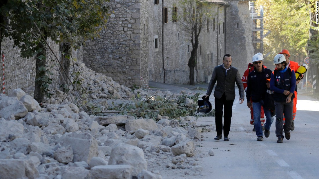 Italian civil protection personnel pass a collapsed wall in Norcia on October 30.