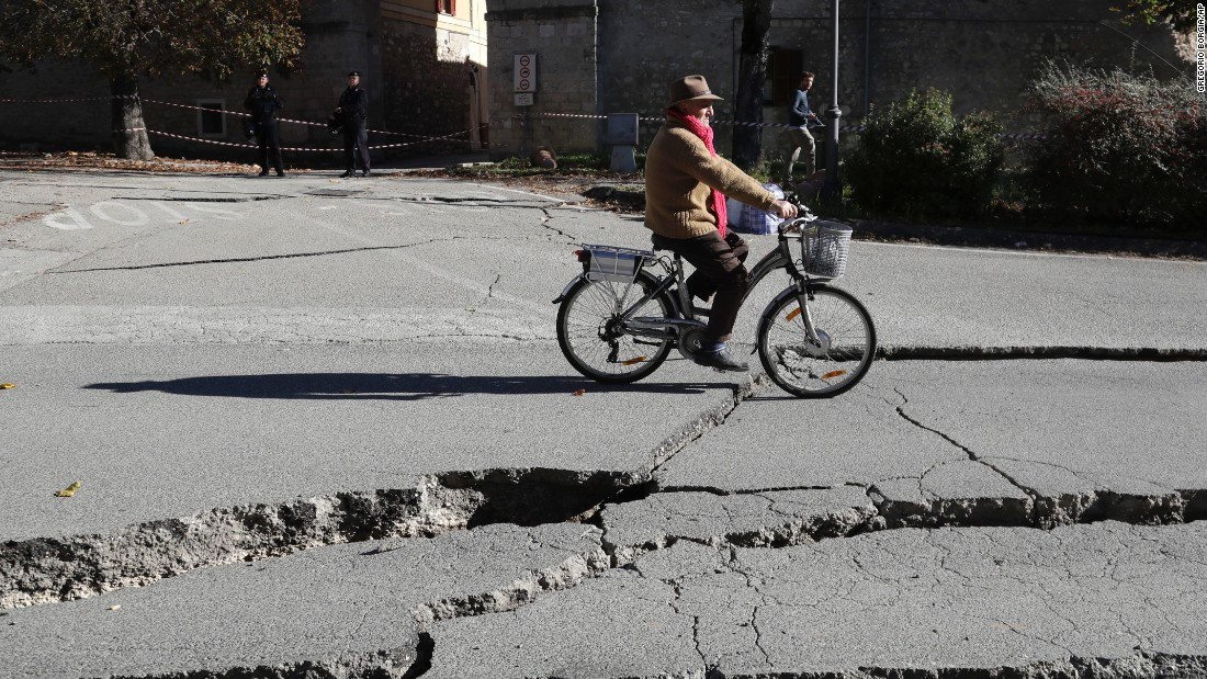A man rides a bicycle past cracks in a road in Norcia on October 30. The quake struck 6 kilometers (3.7 miles) north of Norcia, the US Geological Survey reported.