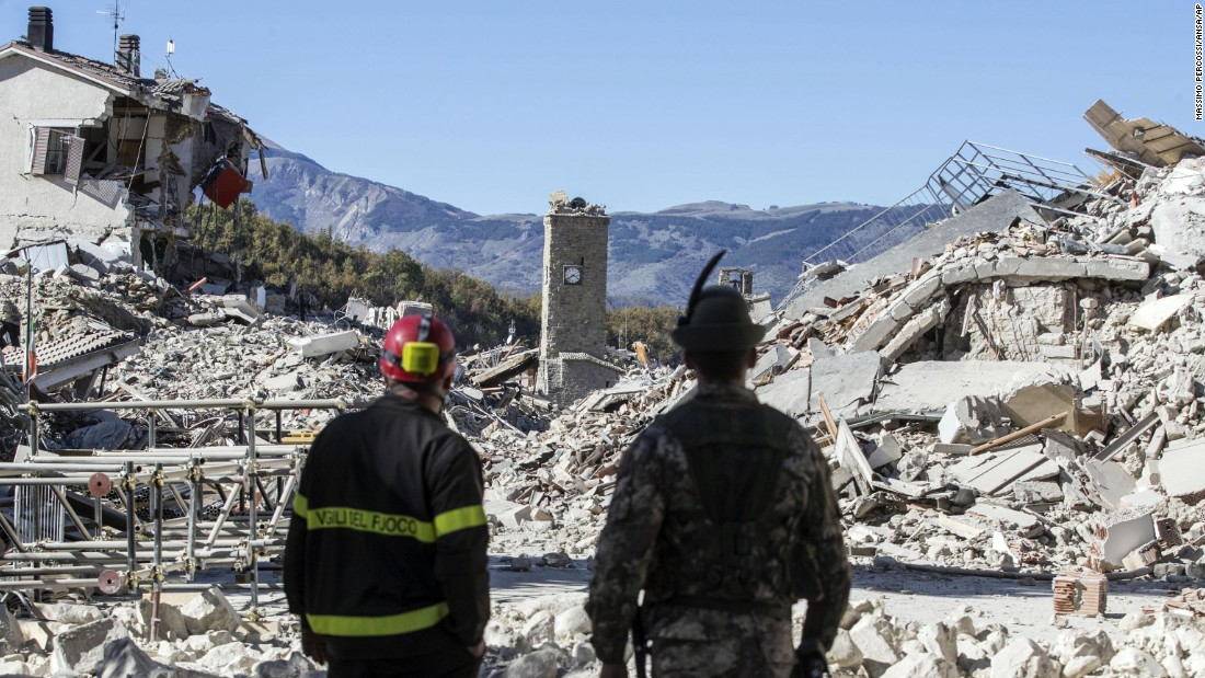 A firefighter and a soldier survey rubble in Amatrice on October 30. The latest quake on Sunday was the strongest to hit the country in more than three decades. Two other quakes struck the same region within the past week. Amatrice's town center also was badly damaged in a deadly temblor in August.